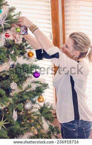 Family decorating beautiful live Christmas tree.