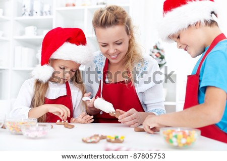 Family decorating christmas cookies together in the kitchen