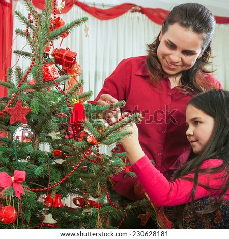 Family decorating Christmas tree At Home