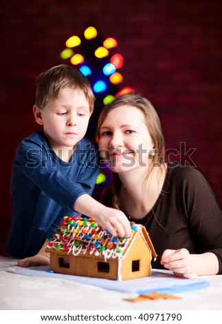 Family decorating gingerbread house at Christmas eve