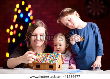 Family decorating gingerbread house on Christmas eve