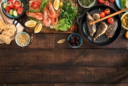 Family dinner table with shrimp, fish grilled, salad, different snacks with border, top view