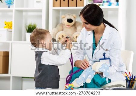 Family doctor examination. Little child visiting pediatrician playing with stethoscope. Beautiful female medical freckled doctor  communicating with cute young patient. Paediatrics medical concept