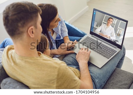 Family doctor online. Family talking consults a doctor using a laptop while sitting at home on the couch.
