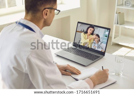 Family doctor online. Male doctor speaks with patients by family using laptop sitting behind straw in clinic office.