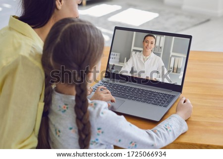 Family doctor online. Mother and girl kid talking consults a doctor using a laptop while sitting at home on the couch.