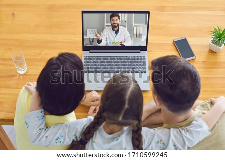 Family doctor online.Parents and a child consult a doctor using a laptop at home.