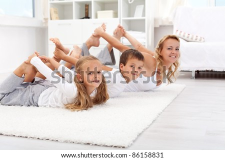 Family doing gymnastic exercises at home - healthy life education
