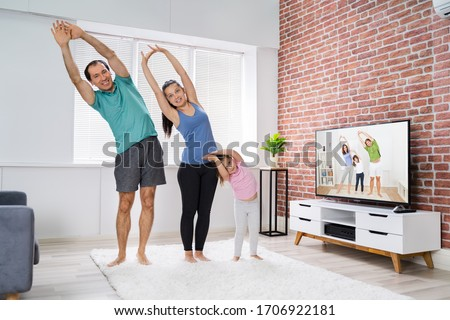 Family Doing Online Stretching Yoga Exercise At Home Foto stock ©