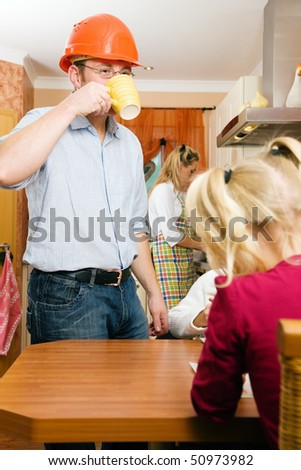 Family doing their breakfast routine in the morning, dad is ready to start to work