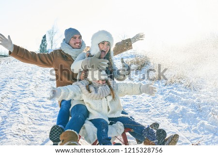 Family doing toboggan in winter and having fun in the snow