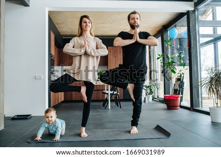 Family doing yoga. Mother and father standing in a position, keeping balance, while their child creeping on all fours at their feet.