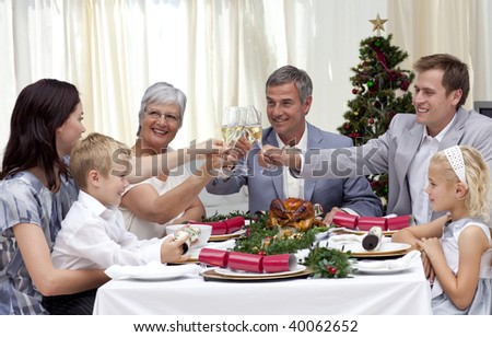 Family drinking a toast in a Christmas dinner at home - stock photo