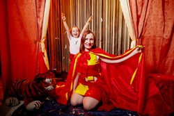 Family during a stylized theatrical circus photo shoot in a beautiful red location. Models mother and daughter posing on stage with curtain