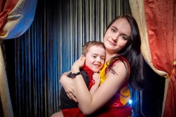 Family during a stylized theatrical circus photo shoot in a beautiful red location. Models mother and son posing on stage with circus curtain
