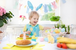 Family Easter breakfast. Child with bunny ears at decorated table with eggs basket, chick and rabbit on Easter morning. Egg hunt and festive meal for kids. Spring home decoration. Boy with dyed eggs.