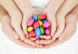 Family Easter - family hands holding brightly colored Easter eggs