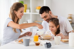family, eating and people concept - happy mother, father and daughter having breakfast at home