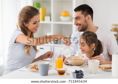 family, eating and people concept - happy mother, father and daughter having breakfast at home Foto stock ©