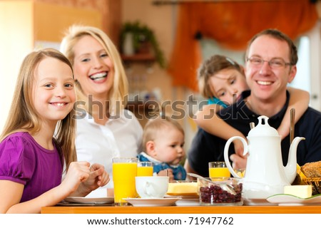 Family eating breakfast in the kitchen of their house