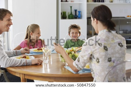 Family eating dinner at round table, in kitchen