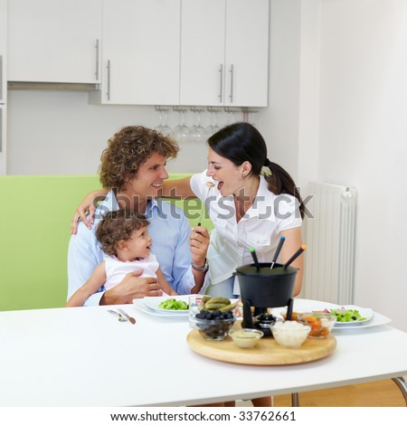 family eating meat fondue at home. Copy space