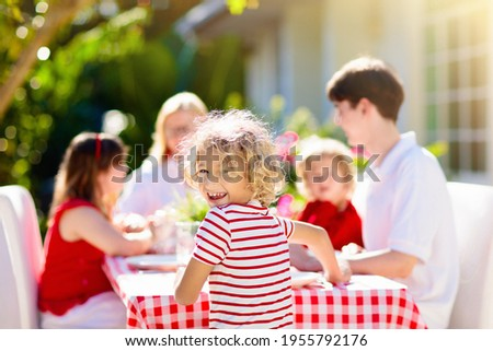 Family eating outdoors. Garden summer fun. Barbecue in sunny backyard. Grandmother and kids eat lunch in outdoor deck. Parents and children enjoy bbq. Boy and girl with mother. Photo stock ©
