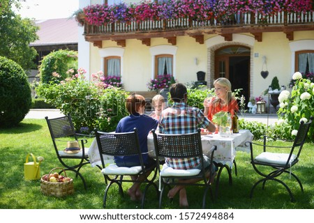 Family eating outdoors in garden