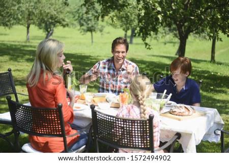 Family eating outdoors in garden