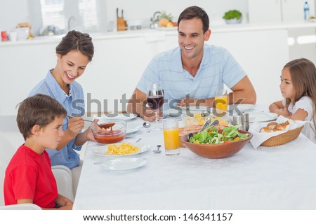 Family eating pasta and salad in the dining room