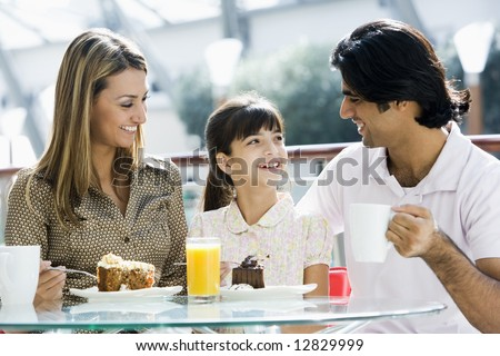 Family eating piece of cake in cafe