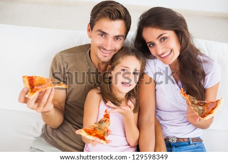 Family eating pizza on a sofa - stock photo