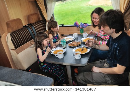Family eating together in RV interior, travel in motorhome (camper, caravan) on vacation - stock photo
