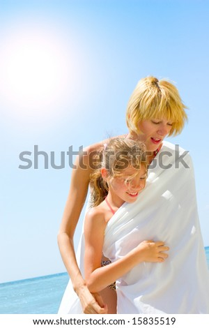 family enjoying beach lifestyle. mother and daughter having fun on the beach