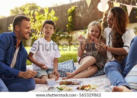 Family Enjoying Picnic On Blanket In Garden