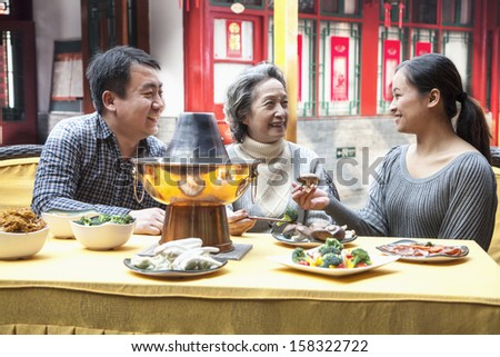 Family enjoying traditional Chinese meal in outdoor restaurant