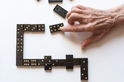 Family entertainment for a fun leisure game of dominoes. The hand of an elderly woman puts a domino on the table.