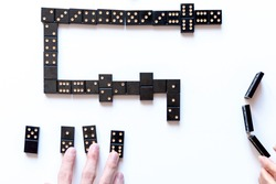 Family entertainment for a fun leisure game of dominoes. The young man's hand holds a domino in his hands