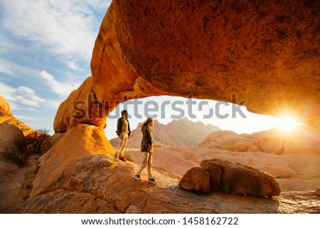 Family father and daughter enjoying sunrise in Spitzkoppe area with picturesque stone arches and unique rock formations in Damaraland Namibia