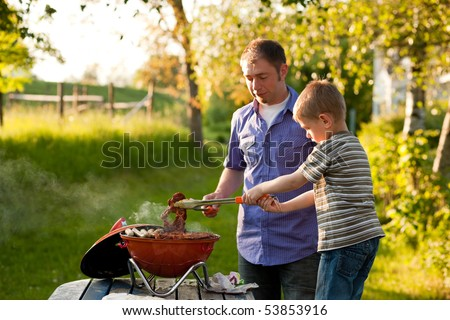 Family - father and son - having a barbecue party, the child is turning meat and sausages, both having fun