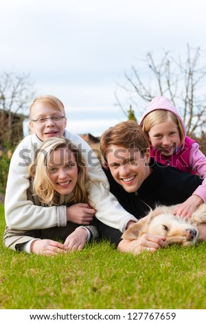 Family, father, mother and daughters, sitting together with their dog on a meadow, they laugh and have fun