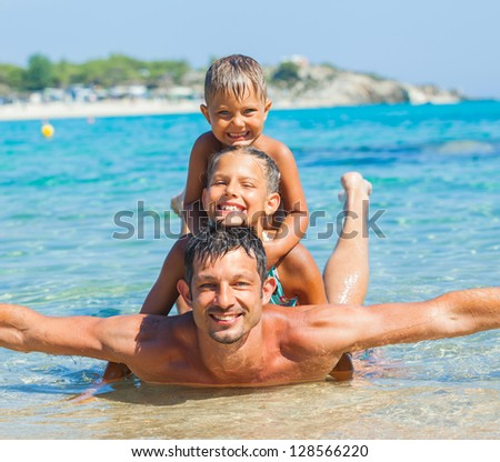 Family - father with his kids have fun and swim in the transparent sea