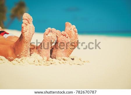 family feet on summer tropical beach