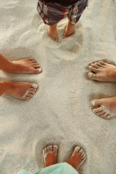 Family feet on the sand on the beach