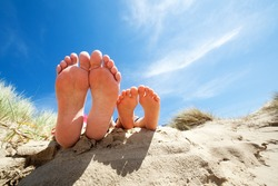 Family feet relaxing and sunbathing on the beach concept for vacation and summer holiday