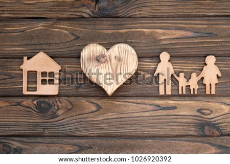 family figures, heart, house against the background of a wooden table. property insurance.