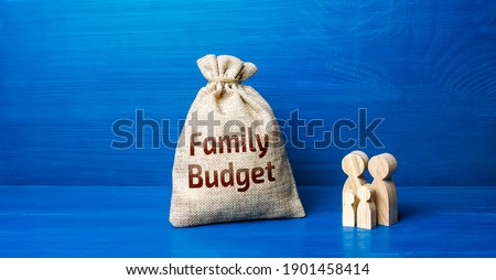 Family figurines and family budget money bag. Security, purchasing power. Financial literacy. Financial support for social institutions. Well-being of the population. Basic income. Cost studies. Foto stock ©