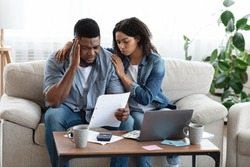 Family Financial Crisis Concept. Depressed Black Couple Looking At Invoice, Not Able To Pay Huge Bills, Suffering From Coronacrisis At Home