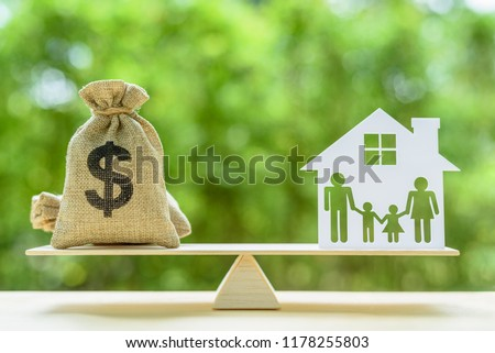 Family financial management, mortgage and payday loan or cash advance concept : Dollar bags, 4 members family under a house or shelter on a balance scale, depicts short term borrowing for a residence.