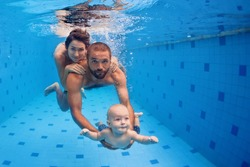 Family fitness - mother, father, baby son learn to swim together, dive underwater with fun in pool Active parent lifestyle, people water sport activity and physical exercises, children swimming lesson